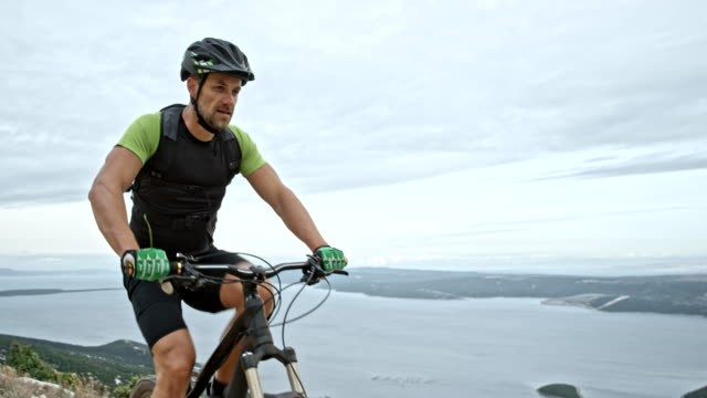 Man riding his mountain bike on a mountain ridge with seashore in the background