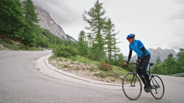 man riding his road bicycle up the asphalt road high in the mountains on a cloudy day - mountain pass stock videos & royalty-free footage