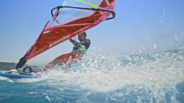 stockvideo's en b-roll-footage met slo mo man rijden zijn windsurf in zon - windsurfen