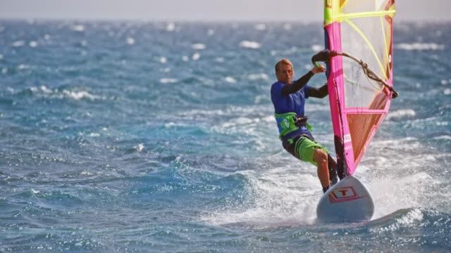 stockvideo's en b-roll-footage met slo mo man rijden zijn windsurf - windsurfen