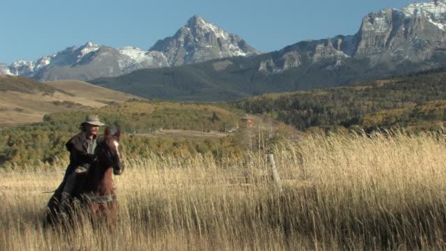 ms, ts, man riding horse through grassland, san juan mountains in background, colorado, usa - 乗馬点の映像素材/bロール