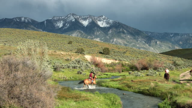 Man Riding Horse Through River in Utah