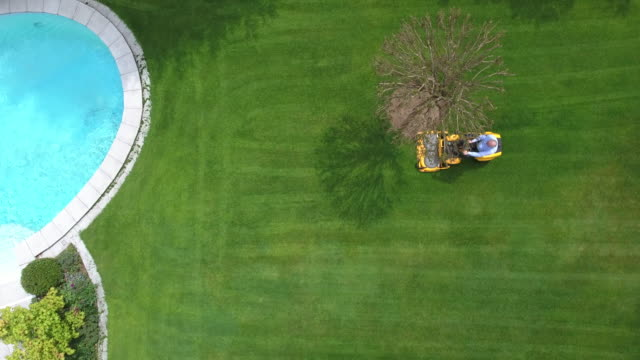 Man riding lawnmower. Aerial view. Back Yard