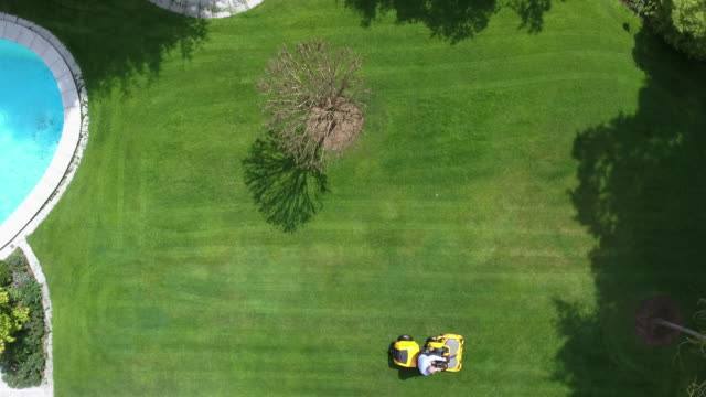 man riding lawnmower. aerial view. back yard - lawn stock videos & royalty-free footage