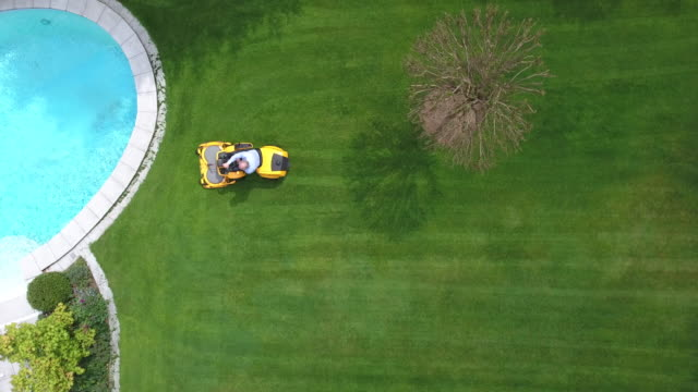 man riding lawnmower. aerial view. back yard - tosaerba video stock e b–roll