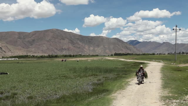 ws td man riding motorbike down dirt road in mountain landscape / lhasa, tibet - only mature men stock videos & royalty-free footage