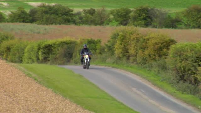 WS TS PAN Man riding motorbike on country road / London, UK