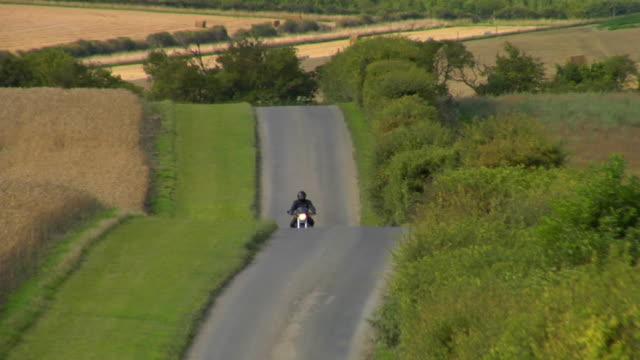 vidéos et rushes de ws td pan man riding motorbike on country road / london, uk - monter sur un moyen de transport