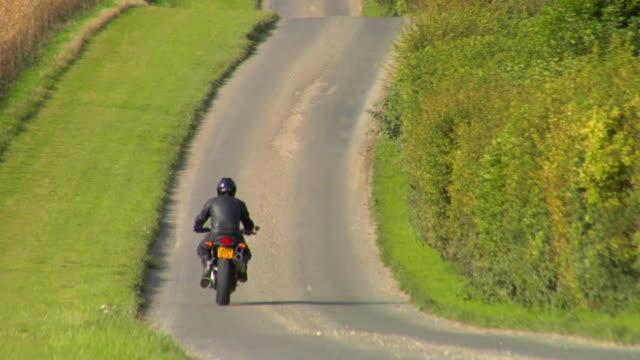 WS TU Man riding motorbike on country road / London, UK
