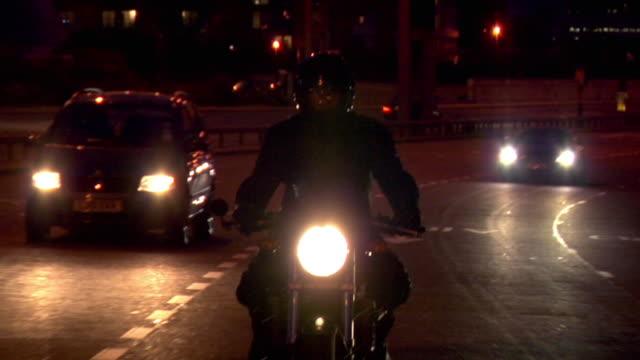 vidéos et rushes de ms pov man riding motorbike on motorway in traffic at night / london, uk - monter sur un moyen de transport