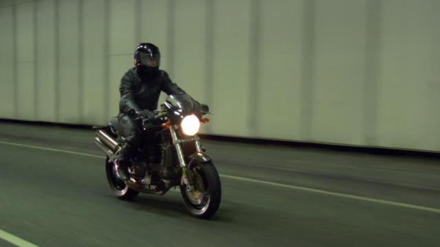 vídeos de stock e filmes b-roll de ws ts man riding motorbike on road in tunnel / london, uk - capacete