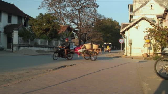 cu zo ws man riding motorbike towing cart, luang prabang, laos - 牛車点の映像素材/bロール