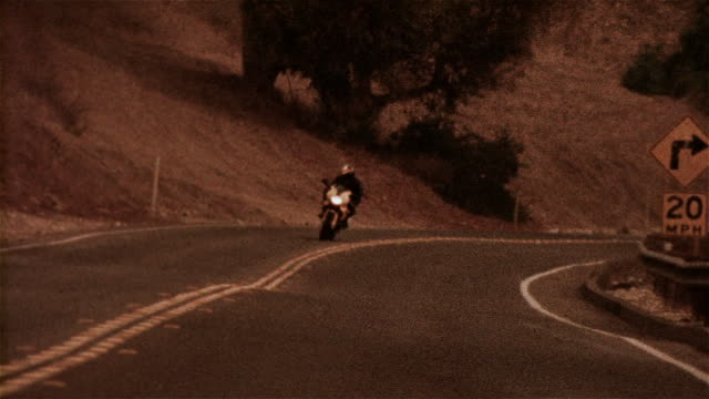 man riding motorcycle around bend - biker jacket stock videos and b-roll footage