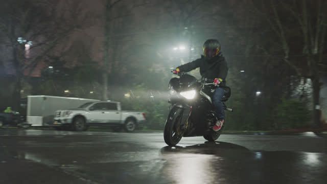 man riding motorcycle on wet street spins to a stop in front of camera on rainy night. - brake stock videos & royalty-free footage