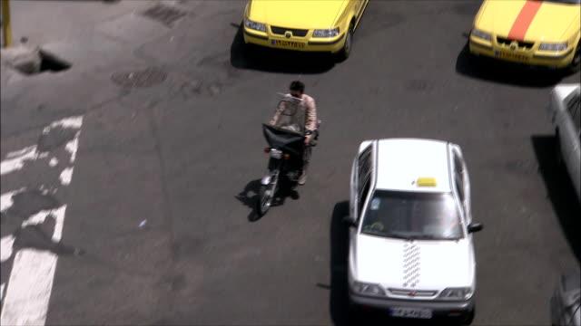 ms ha ts man riding motorcycle through heavy traffic on street, tehran, iran - tehran stock videos & royalty-free footage