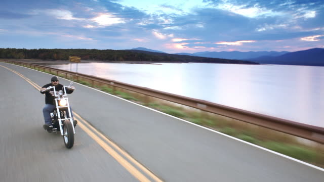 MS POV Man riding motorcycles on country road with along lake and mountains at sunset / West Hurley, New York, United States