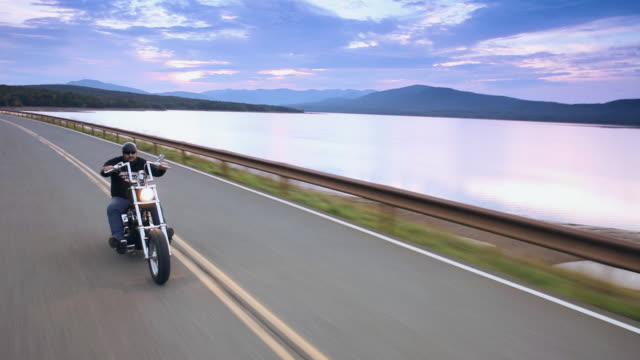 vídeos de stock, filmes e b-roll de ms pov man riding motorcycles on country road with along lake and mountains at sunset / west hurley, new york, united states - motocicleta