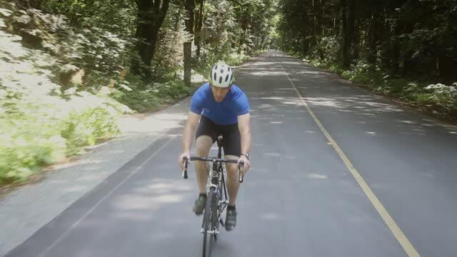 WS POV Man riding mountain bike on road through forest / Squamish/Whistler, British Columbia, Canada
