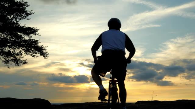 man riding mountain bike to the summit at sunset - 腰に手を当てる点の映像素材/bロール