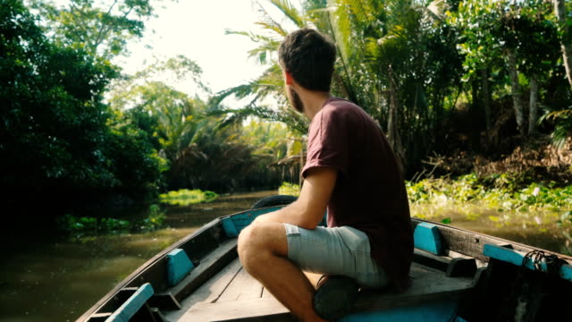 man riding on boat through mekong delta - mekong delta stock videos & royalty-free footage