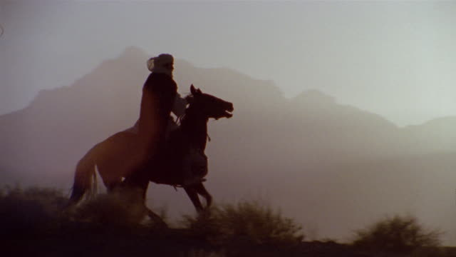 vidéos et rushes de slo mo ws pan reenactment man riding on horse through desert and horse rears up / iran - reconstitution