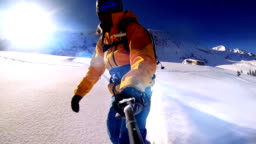 Man riding on snowboard with selfie stick in his hand