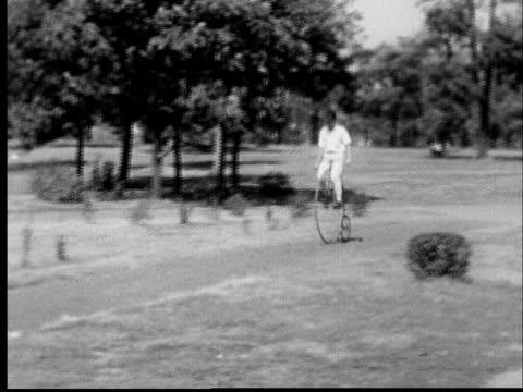 vídeos y material grabado en eventos de stock de 1935 ws pan man riding penny-farthing bicycle through park - bicicleta vintage