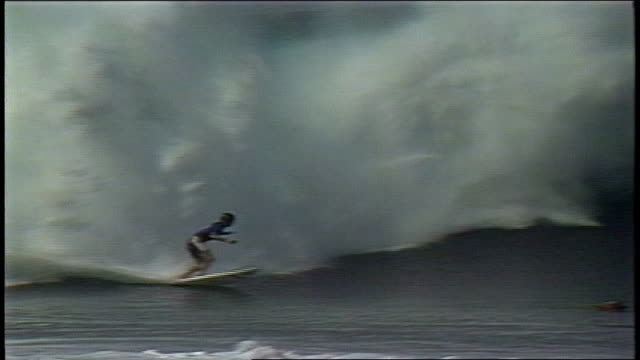 vídeos de stock, filmes e b-roll de man riding pipeline wave and wiping out in pupukea hawaii - pipeline wave