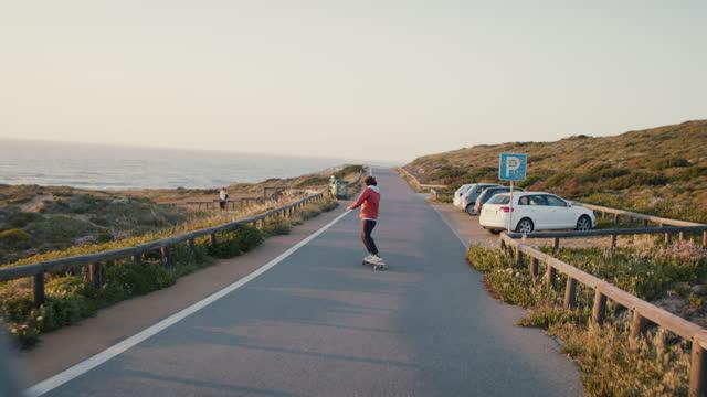 man riding skateboard at sunset by ocean - kryssa bildbanksvideor och videomaterial från bakom kulisserna