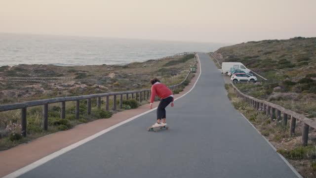 vídeos y material grabado en eventos de stock de man riding skateboard on ocean road - pasear en coche sin destino