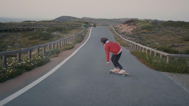 stockvideo's en b-roll-footage met man riding skateboard on ocean road - rondrijden