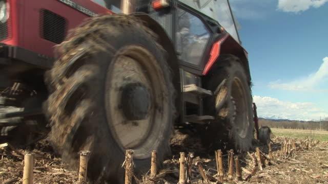 LA CU Man riding tractor on field and preparing land for farming in Ljubljansko Barje / Notranjska, Slovenia