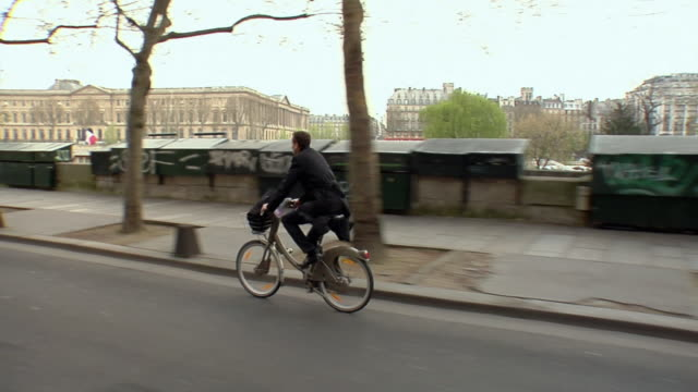 WS TS Man riding Velib bike on street, Paris, France
