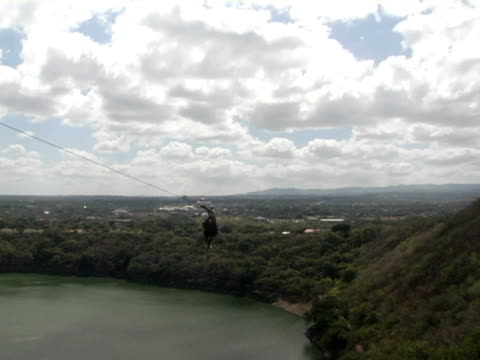 stockvideo's en b-roll-footage met ws, pan, man riding zip line canopy tour above lagoon - managua