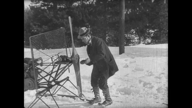 1922 Man (Buster Keaton) rigs ski vehicle, sending would be follower into reverse