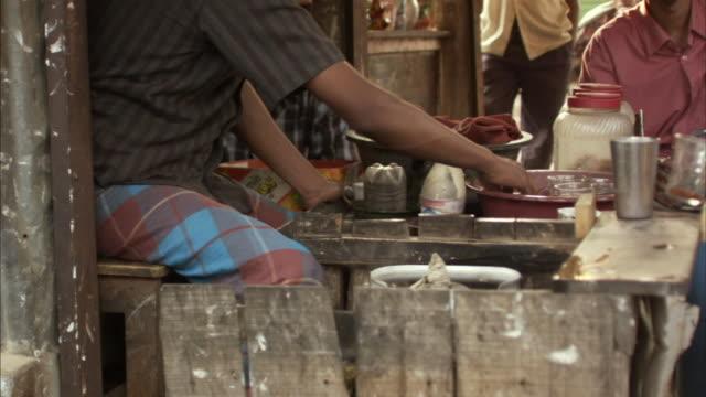 ms, tu, man rinsing glass in bowl sitting next to other men in tea shop, mawna, bangladesh - dhaka stock videos and b-roll footage