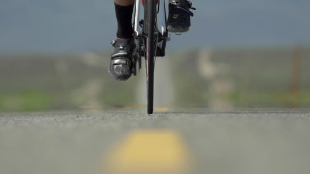 vídeos y material grabado en eventos de stock de a man road biking on a scenic desert road. - slow motion - pantalón corto