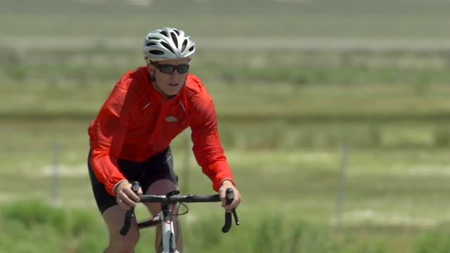 vídeos de stock, filmes e b-roll de a man road biking on a scenic road. - slow motion - goodsportvideo