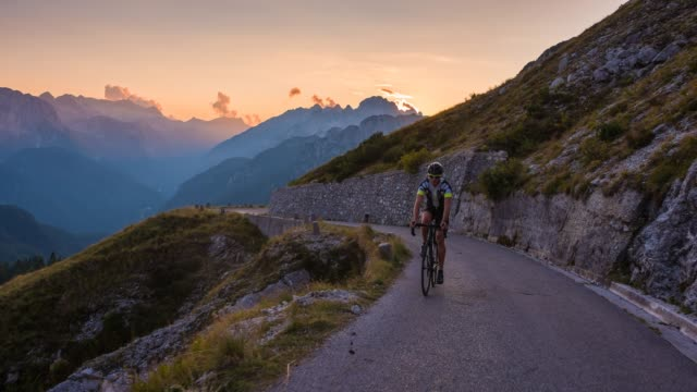 man road cycling uphill on a beautiful summer evening, layered mountains in background - high up stock videos & royalty-free footage