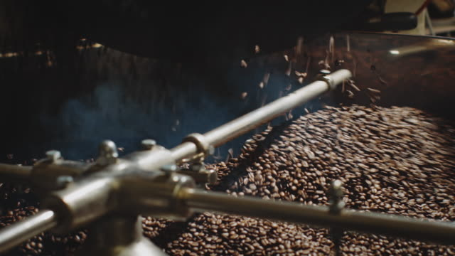 man roasting coffee beans at factory - coffee drink stock videos & royalty-free footage
