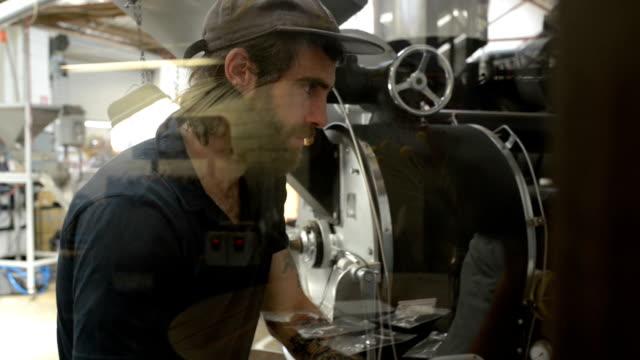 vidéos et rushes de homme de torréfaction des grains de café avec la machine - casquette