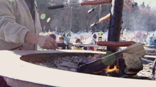 4k man roasting sausages over open fire at ski resort, slow motion - ski resort stock videos & royalty-free footage