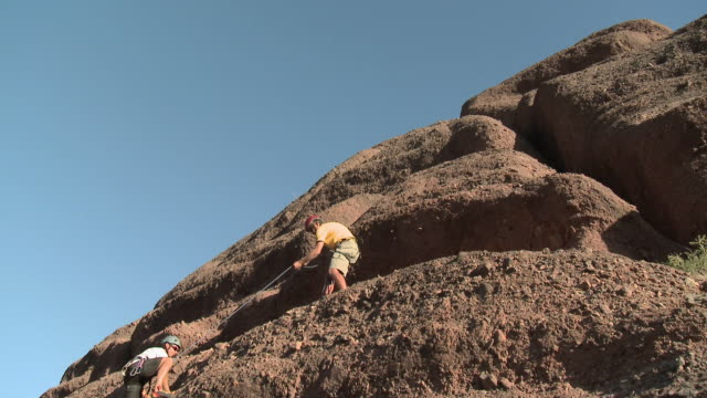 stockvideo's en b-roll-footage met man rock climbing as other climber helps him up, they high five - argentijnse etniciteit