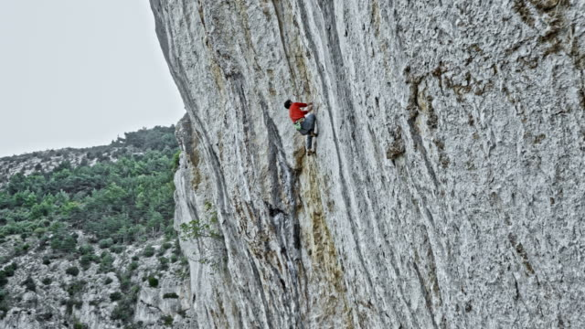 aerial man rock climbing up a cliff - krab stock videos & royalty-free footage