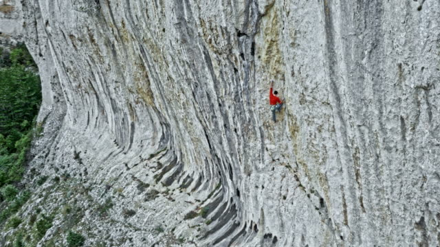 aerial man rock climbing up a cliff wall - zoom in stock videos & royalty-free footage