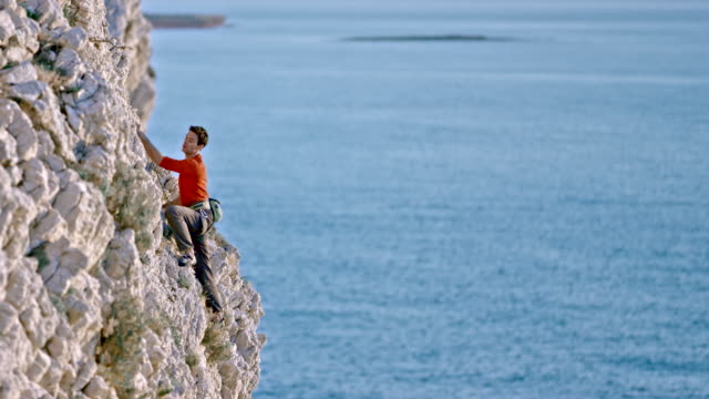 Man rock climbing up a jagged cliff above the sea in sunshine