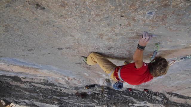 vidéos et rushes de a man rock climbing up a mountain. - lutte concepts