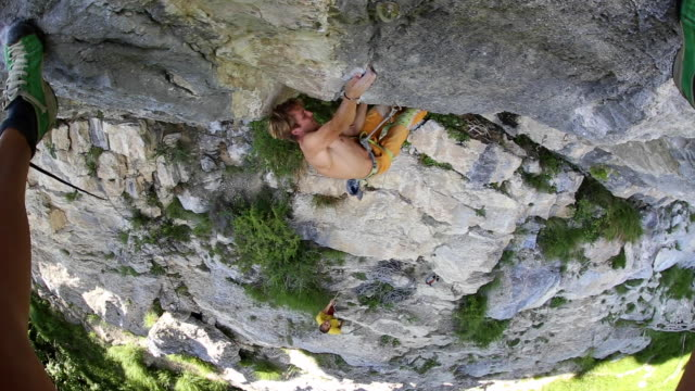 a man rock climbing up a mountain. - nackter oberkörper stock-videos und b-roll-filmmaterial