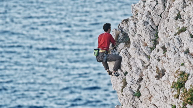 Man rock climbing up a rugged cliff wall