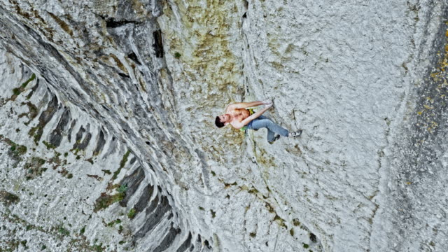 vídeos de stock e filmes b-roll de aerial man rock climbing up a steep wall of a cliff - equipamento de alpinismo